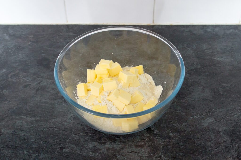 A glass bowl filled with cubed butter, flour salt and sugar on a kitchen worktop.