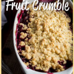 """Close up left side view of apple berry Summer fruit crumble on a piece of frayed hessian fabric over a wooden worktop. There are berries, leaves an apple and a tea towel in the background. A text overlay says 'Apple berry Summer fruit crumble""""."""