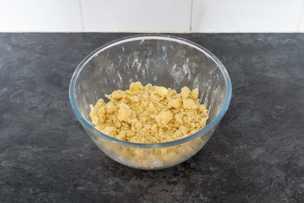 A glass bowl filled with a crumble mixture on a kitchen worktop.