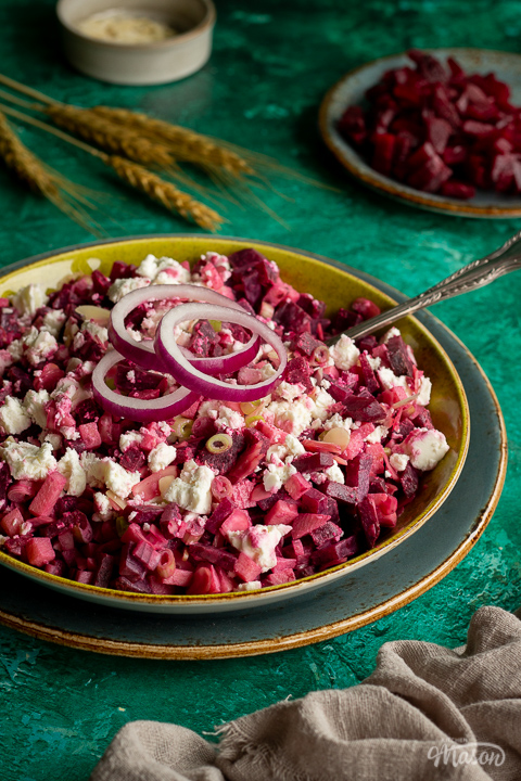 Side angle of apple and beetroot salad in a green serving dish on a dark green plate with a spoon inside. Set on a bright green backdrop with a light brown linen napkin, a plate of diced beetroot, some wheat and a pot of flaked almonds in the background.