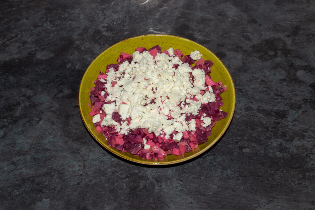 Apple and beetroot salad in a green serving bowl topped with creamy feta cheese.