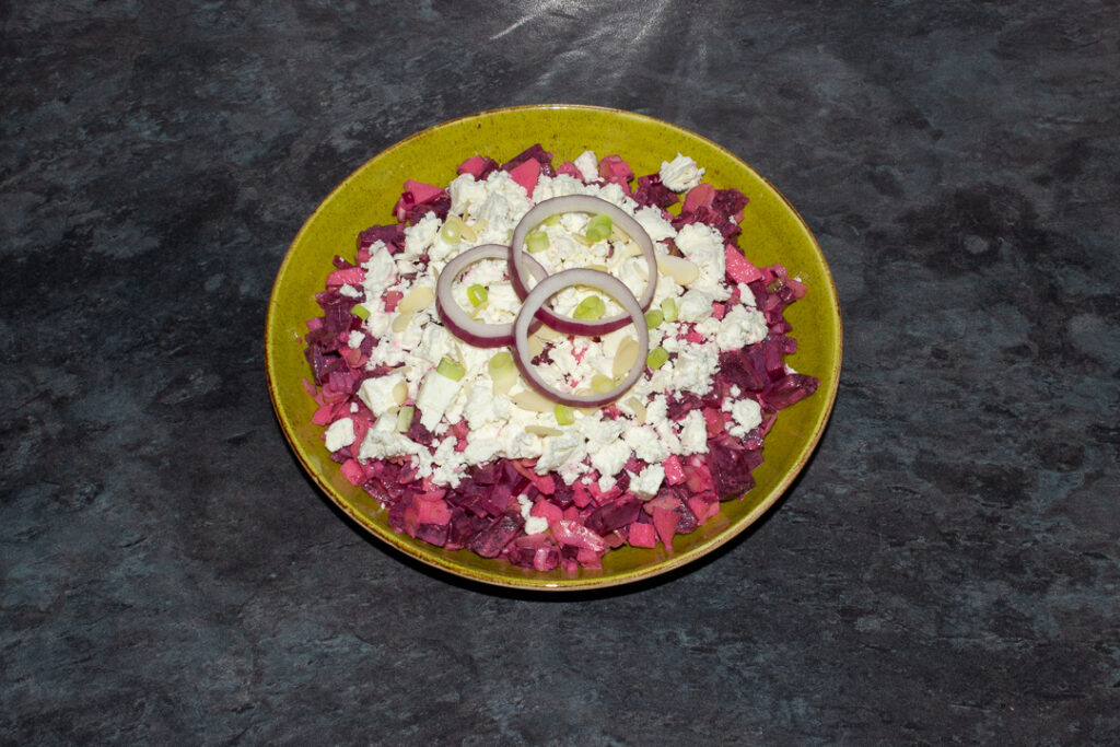 Apple and beetroot salad in a green serving bowl topped with creamy feta cheese, flaked almonds, spring onion and 3 rings of red onion.