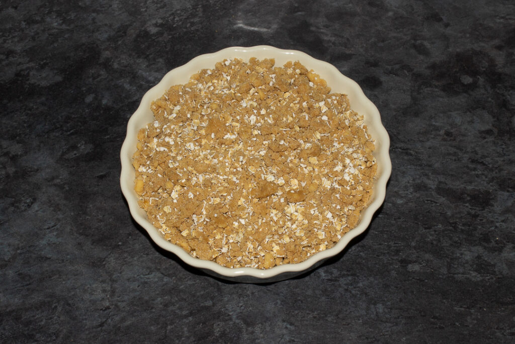 Peach mixture in a fluted ceramic serving dish topped with the crisp mixture.