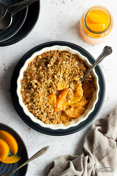Peach crisp in a fluted ceramic serving dish set on a blue plate with a serving spoon inside. There's a light brown linen napkin, a blue plate of peaches with a fork, a jar of peaches and 2 stacked blue plates with spoons on top in the background. Set over a light mottled backdrop.