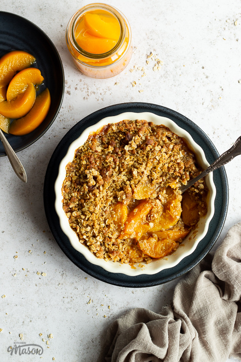 Peach crisp in a fluted ceramic serving dish set on a blue plate with a serving spoon inside. There's a light brown linen napkin, a blue plate of peaches with a fork and a jar of peaches in the background. Set over a light mottled backdrop.
