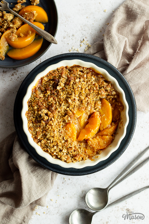 Peach crisp in a fluted ceramic serving dish set on a blue plate over a light brown linen napkin. There are two spoons and a blue plate with peach crisp on it in the background. Set over a light mottled backdrop.