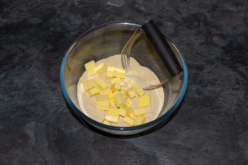 Flour, brown sugar and salt mixed together with cold cubed butter on top in a glass bowl with a pastry blender on a grey worktop.