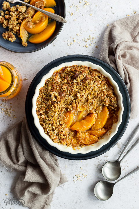 Peach crisp in a fluted ceramic serving dish set on a blue plate over a light brown linen napkin. There are two spoons, a blue plate with peach crisp on it and a jar of peaches in the background. Set over a light mottled backdrop.