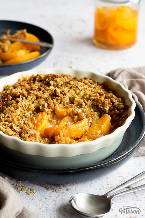 Side view of peach crisp in a fluted ceramic serving dish set on a blue plate. There's a light brown linen napkin, a blue plate of peaches with a fork, a jar of peaches and two spoons in the background. Set over a light mottled backdrop.