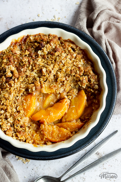 Close up of peach crisp in a fluted ceramic serving dish set on a blue plate over a light brown linen napkin. There are two spoons in the background and it's all set over a light mottled backdrop.