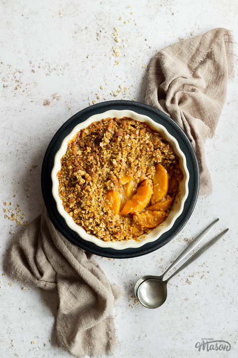 Peach crisp in a fluted ceramic serving dish set on a blue plate over a light brown linen napkin. There are two spoons in the background and it's all set over a light mottled backdrop.