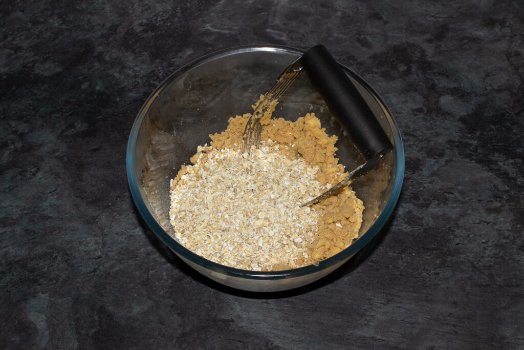 Flour, brown sugar, salt and butter mixed together with oats on top in a glass bowl with a pastry blender on a grey worktop.