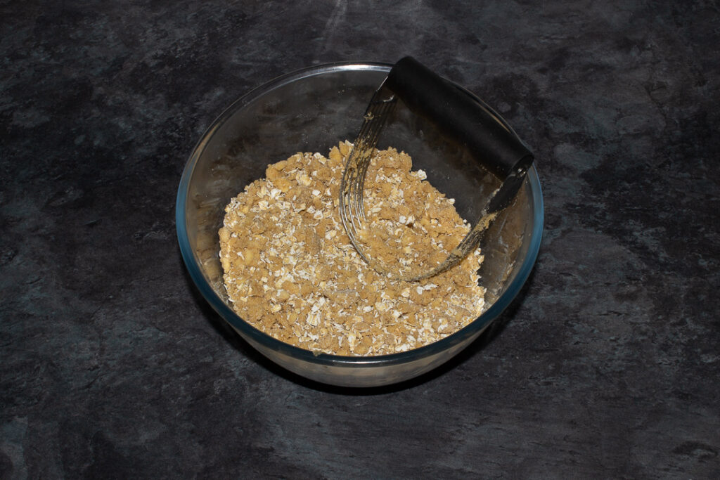Flour, brown sugar, salt, butter and oats mixed together in a glass bowl with a pastry blender on a grey worktop.