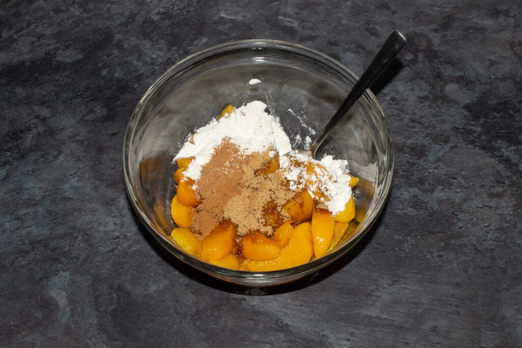 Drained tinned peaches, brown sugar, flour, nutmeg and cinnamon in a glass bowl with a metal spoon set on a grey worktop.