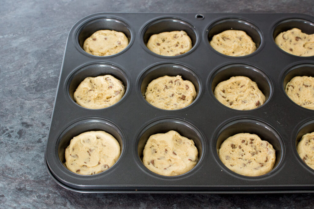 Cookie dough pressed into the holes of a cupcake/muffin tin on a kitchen worktop.