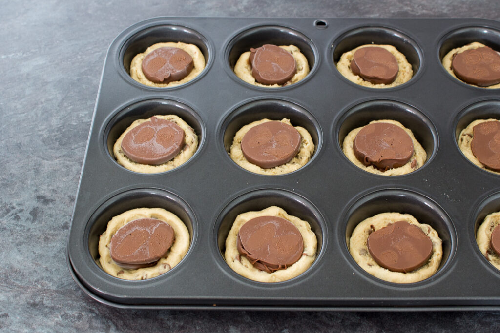 Cookie dough pressed into the holes of a cupcake/muffin tin with frozen Nutella blobs on top on a kitchen worktop.