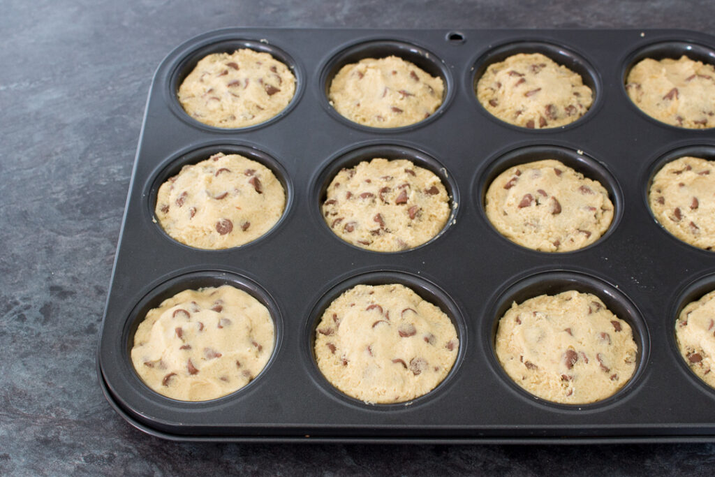 Unbaked Nutella Lava Cookies in a cupcake/muffin tin ready to be baked in the oven.