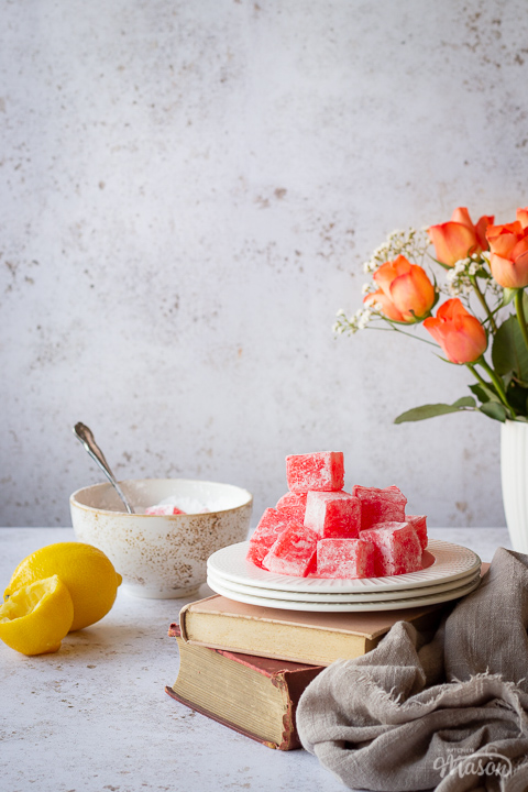 Distanced front view of a white plate filled with homemade Turkish delight set on top of two old books. There's a light brown linen napkin resting against the books and squeezed lemon halves, a bowl of icing sugar with a spoon and a white mug filled with orange roses in the background. All set on a white mottled backdrop.