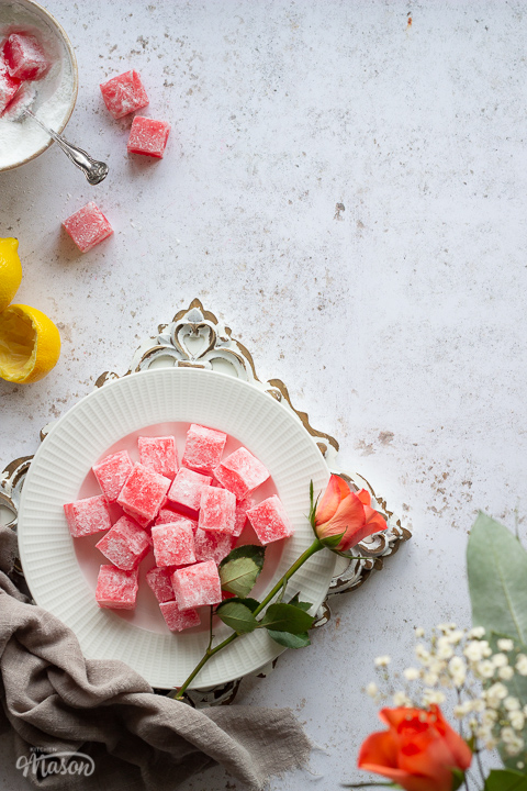 A vertical flat lay view of homemade Turkish delight on a white plate with an orange rose on the side, set on a rustic white wood board. There's a light brown linen napkin resting next to the plate, a bowl filled with icing sugar Turkish delight and a spoon, squeezed lemon halves and orange roses in the background. All set on a white mottled backdrop.