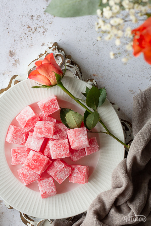 A close up flat lay view of homemade Turkish delight on a white plate with an orange rose set on a rustic white wooden board. There's a light brown linen napkin and more orange roses in the background, all set on a white mottled backdrop.