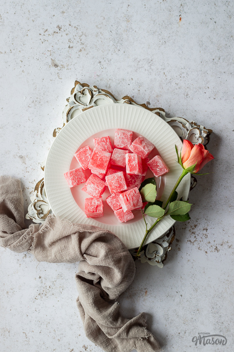 Homemade Turkish delight on a white plate with an orange rose set on a square rustic white board over a mottled white backdrop. There is a light brown linen napkin resting against the side.