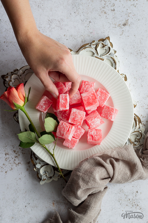 Close up of homemade Turkish delight on a white plate with an orange rose set on a square rustic white board over a mottled white backdrop. There is a light brown linen napkin resting against the side and a hand reaching in to take a piece.