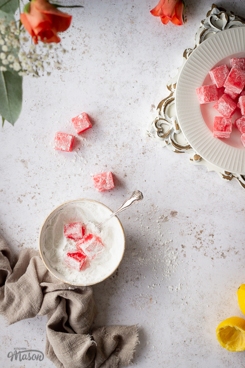 A flat lay view of homemade Turkish delight in a bowl of icing sugar with a spoon. There's a light brown linen napkin resting next to it and squeezed lemon halves, orange roses, a plate of more Turkish delight on a white plate over a rustic white board and several pieces scattered around in the background. All set on a white mottled backdrop.