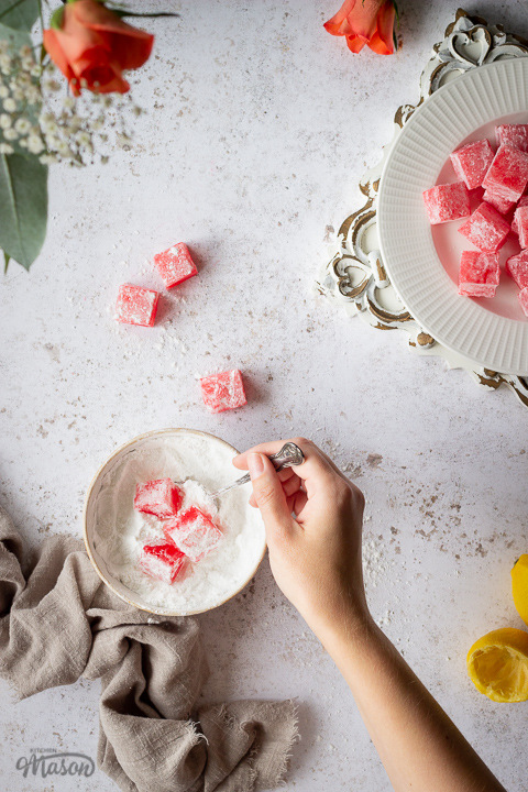 A flat lay view of homemade Turkish delight in a bowl of icing sugar with a spoon being held by a hand. There's a light brown linen napkin resting next to it and squeezed lemon halves, orange roses, a plate of more Turkish delight on a white plate over a rustic white board and several pieces scattered around in the background. All set on a white mottled backdrop.