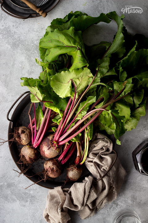 A bunch of whole beetroot complete with leaves covered in soil on a dark grey metal tray with a light brown linen napkin resting at the side. There is also an open jar of pickled beetroot, an empty pickling jar and a couple of stacked grey metal plates with a wooden fork on top in the background. Set over a brushed grey backdrop.