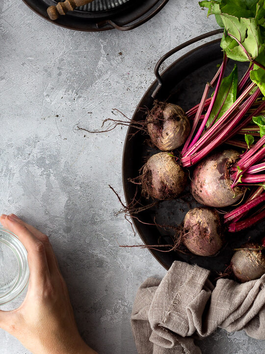 A bunch of whole beetroot complete with leaves covered in soil on a dark grey metal tray with a light brown linen napkin resting at the side. There is also an open jar of pickled beetroot, an empty pickling jar with a hand holding it, a beetroot stained lid and a couple of stacked grey metal plates with a wooden fork on top in the background. Set over a brushed grey backdrop.