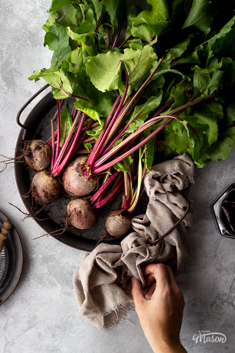 A bunch of whole beetroot complete with leaves covered in soil on a dark grey metal tray with a light brown linen napkin resting at the side and a hand holding it. There is also an open jar of pickled beetroot and a couple of stacked grey metal plates with a wooden fork on top in the background. Set over a brushed grey backdrop.