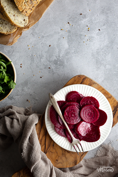 Close up view of a white plate filled with pickled beetroot topped with a fork, on top of a wooden chopping board. Set over a brushed grey backdrop there is also a light brown linen napkin, a bowl of salad leaves and some sliced bread in the background.