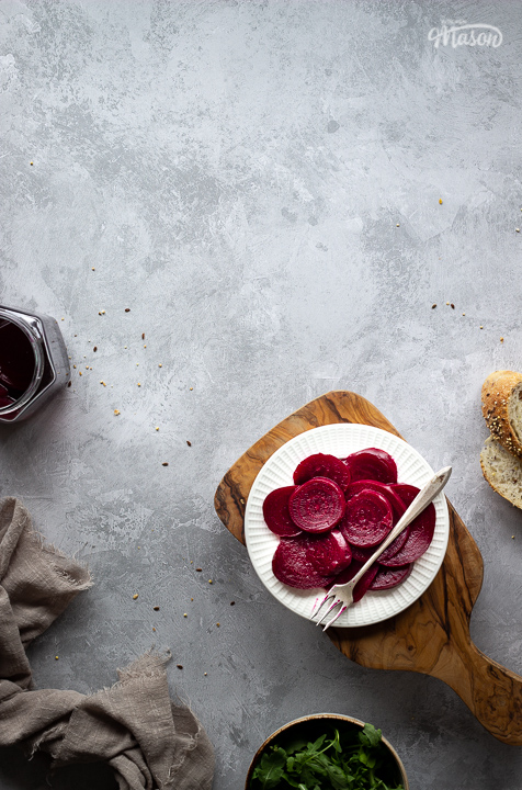 A white plate filled with pickled beetroot topped with a fork, on top of a wooden chopping board. Set over a brushed grey backdrop there is also an open jar of pickled beetroot, a light brown linen napkin, a bowl of salad leaves and some sliced bread in the background.