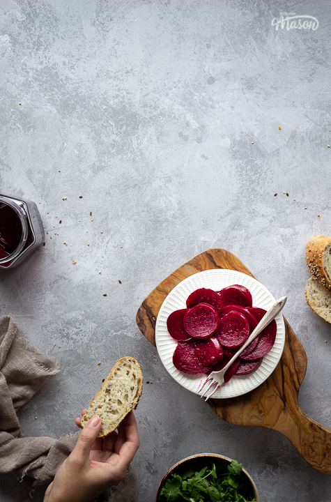 A white plate filled with pickled beetroot topped with a fork, on top of a wooden chopping board. Set over a brushed grey backdrop there is also an open jar of pickled beetroot, a light brown linen napkin, a bowl of salad leaves, some sliced bread and a hand holding a piece of bread in the background.