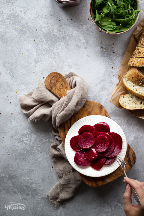 A white plate filled with pickled beetroot with a hand reaching in with a fork to take a piece, on top of a wooden chopping board. Set over a brushed grey backdrop there is also an open jar of pickled beetroot, a light brown linen napkin, a bowl of salad leaves and some sliced bread in the background.