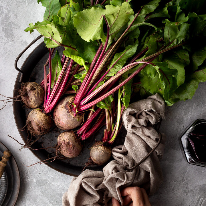Close up of a bunch of whole beetroot complete with leaves covered in soil on a dark grey metal tray with a light brown linen napkin resting at the side and a hand holding it. There is also an open jar of pickled beetroot and a couple of stacked grey metal plates with a wooden fork on top in the background. Set over a brushed grey backdrop.