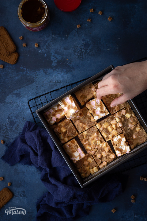 A square baking tin filled with bars of Biscoff rocky road with a hand reaching in for a piece ,set on a wire cooling rack with a blue linen napkin. There is also an open jar of Biscoff spread, some Biscoff biscuits and some fudge pieces scattered around in the background. All set on a deep blue backdrop.