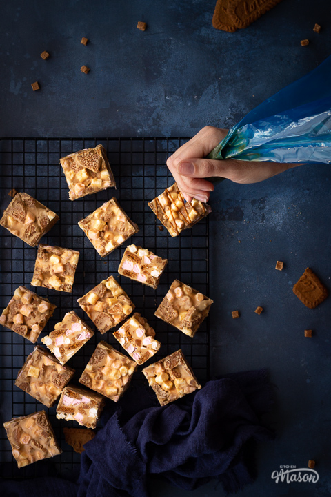 Biscoff rocky road bars on a wire cooling rack with a blue linen napkin and some broken Biscoff biscuits. There's a hand holding a piping bag of melted Biscoff spread drizzling zigzags over the bars. Set on a blue backdrop, there are also a few fudge pieces and more broken Biscoff biscuits scattered around in the background.