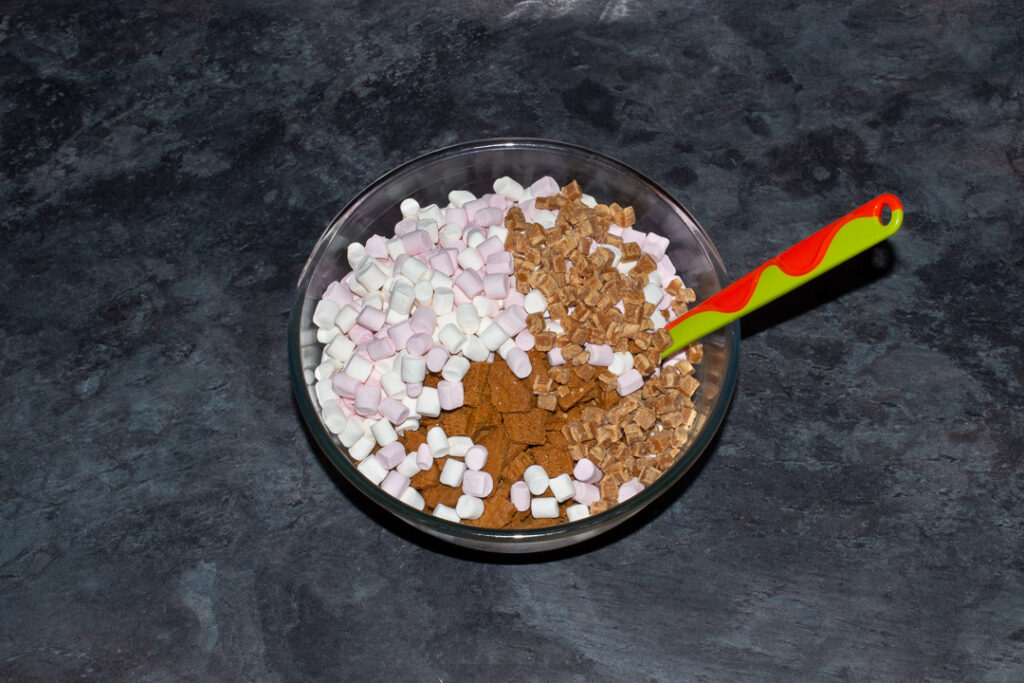 A large glass bowl on a kitchen worktop filled with a melted white chocolate and Biscoff mixture, mini marshmallows, chopped Biscoff biscuits and fudge pieces.