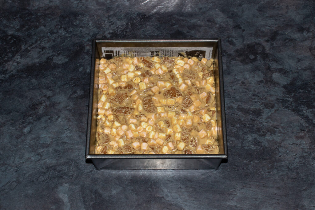 A lined square baking tin on a kitchen worktop filled with Biscoff rocky road.