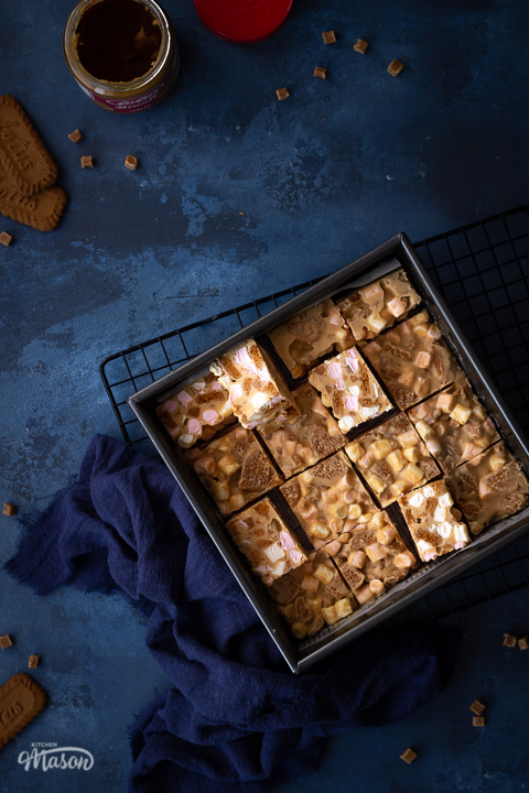 A square baking tin filled with bars of Biscoff rocky road set on a wire cooling rack with a blue linen napkin. There is also an open jar of Biscoff spread, some Biscoff biscuits and some fudge pieces scattered around in the background. All set on a deep blue backdrop.