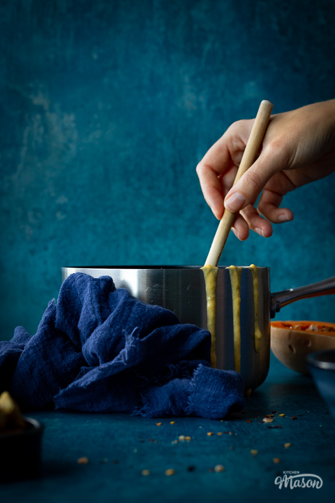 Someone stirring with a wooden spoon in a saucepan of butternut squash soup set against a teal backdrop. There are drips of soup down the side of the pan, half a butternut squash, a pot of croutons and a blue linen napkin in the backgtround.