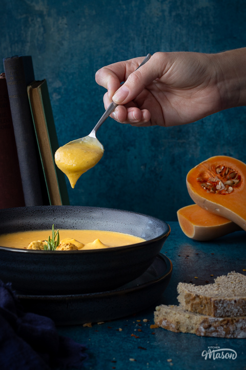 Front view of a bowl of spicy roast butternut squash soup with a hand holding up a spoon filled with soup above it set over a plate. There is a dark blue linen napkin, some books stacked up at the back, two halves of a butternut squash and some bread in the background. Set on a teal backdrop.