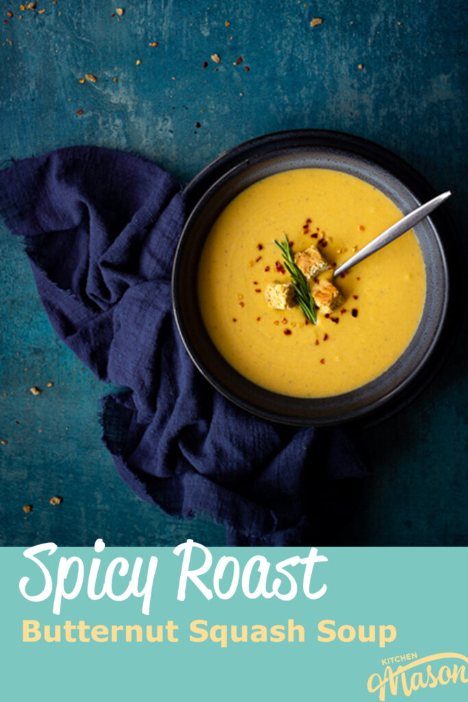 """Flat lay view of spicy roast butternut squash soup with a spoon in a blue bowl set on a blue plate with a dark blue linen napkin on the side. Set on a teal backdrop, there are a few chilli flakes and breadcrumbs scattered in the background. A text overlay says """"spicy roast butternut squash soup""""."""