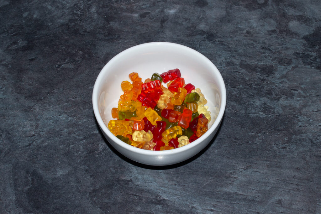 Gummy bears in a white bowl on a kitchen worktop.