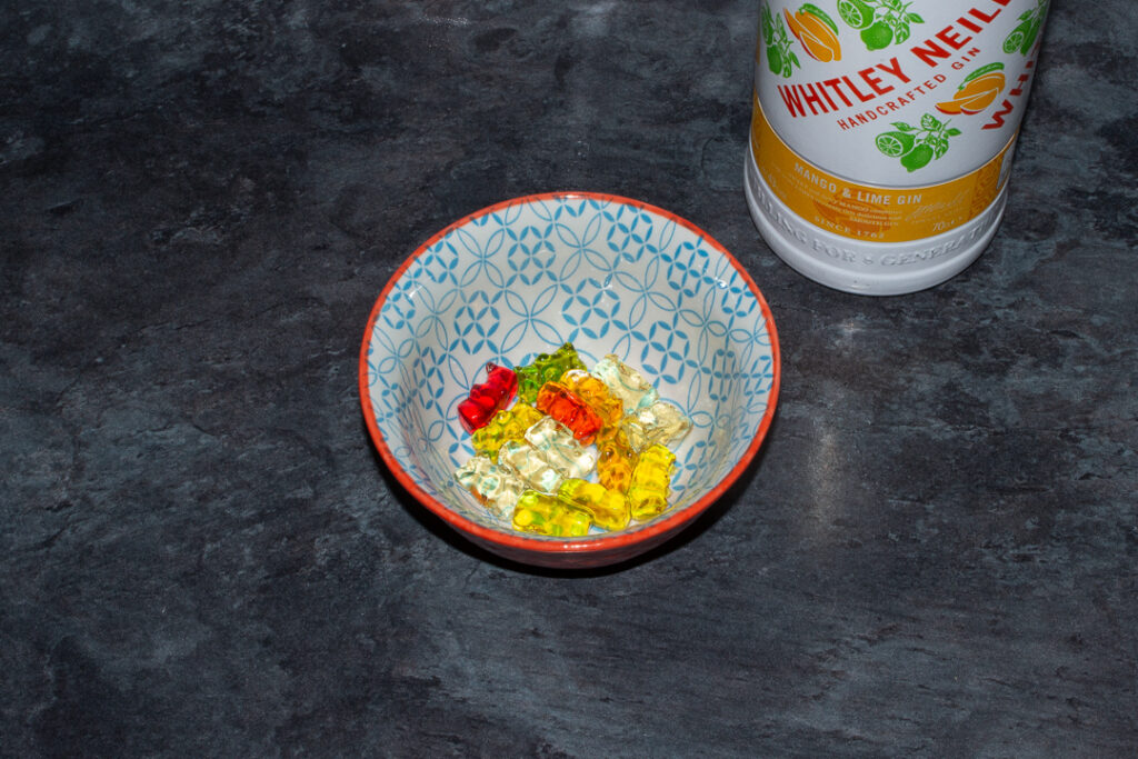 Rinsed mango and lime gin soaked gummy bears in a bowl on a kitchen worktop. There's a bottle of mango and lime gin in the background.