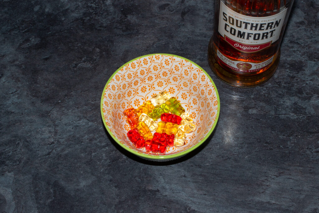 Rinsed Southern Comfort soaked gummy bears in a bowl on a kitchen worktop. There's a bottle of Southern Comfort in the background.