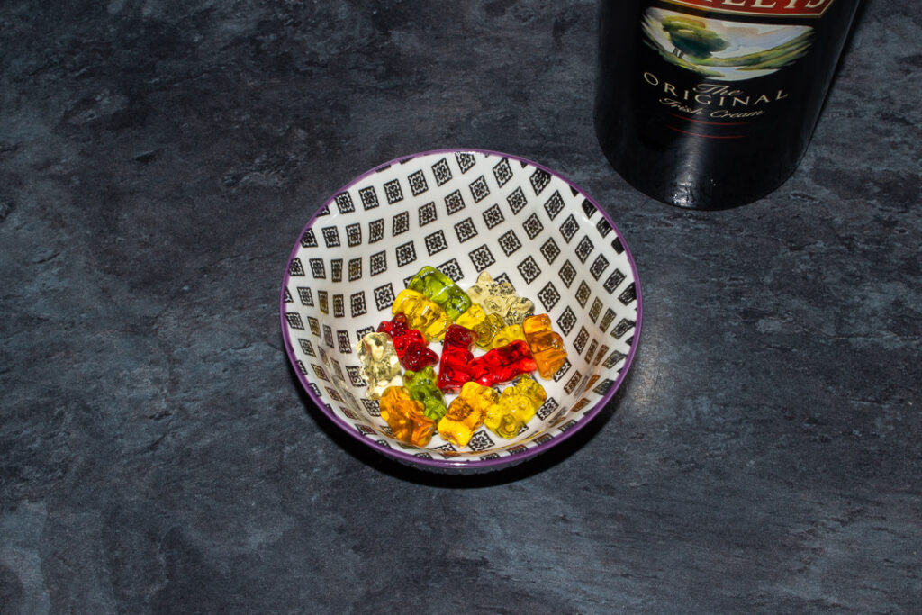 Rinsed Baileys soaked gummy bears in a bowl on a kitchen worktop. There's a bottle of Baileys in the background.