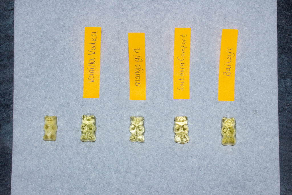 A piece of kitchen paper with an original unsoaked gummy bear on it followed by gummy bears soaked in each of the 4 tested spirits. (There are labels stating which one each gummy bear hs been soaked in.)