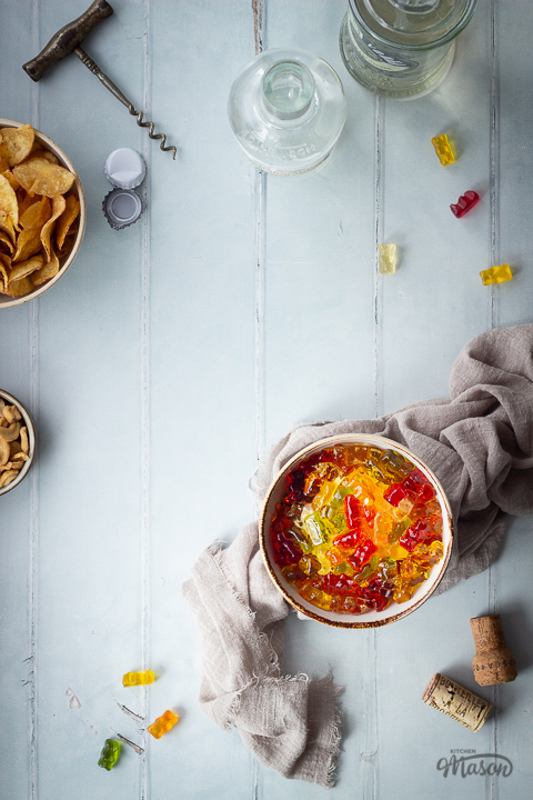 Flat lay view of vodka gummy bears in a bowl over a light brown linen napkin. There is also a bowl of crisps, a bowl of cashew nuts, 2 bottles of spirits, a cork screw, 2 bottle tops, 2 corks and gummy bears in the background. Set over a pale green wood effect backdrop.